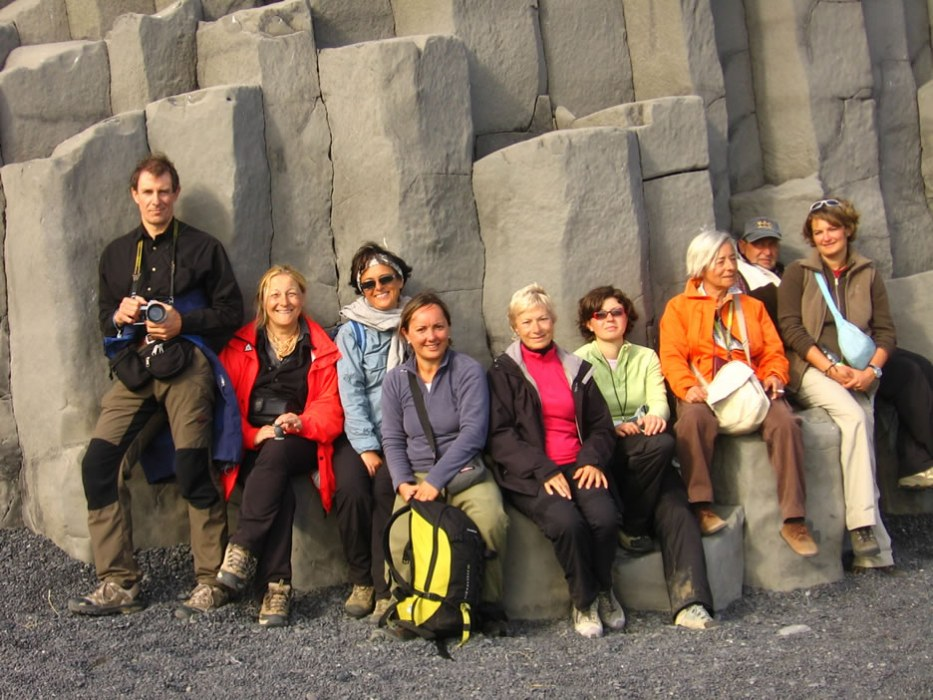 turisti davanti a colonne di basalto a Vik